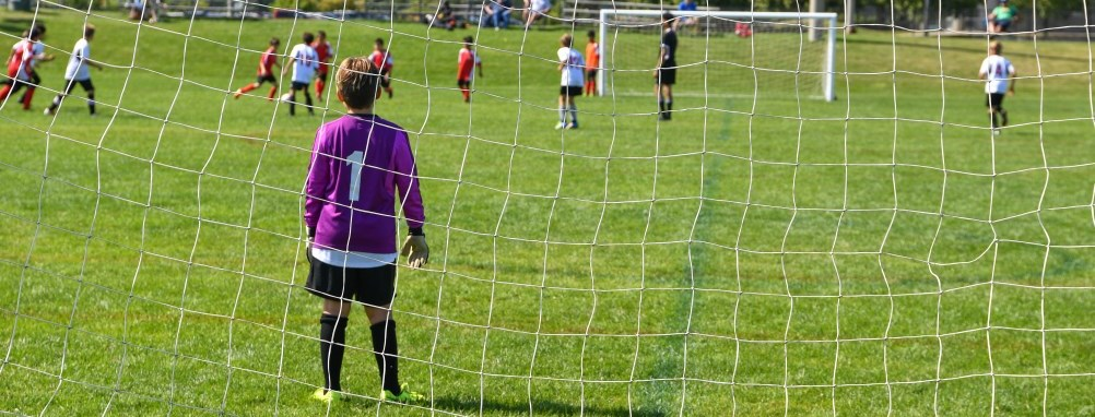 A goalie on the soccer field minding the net at a soccer game