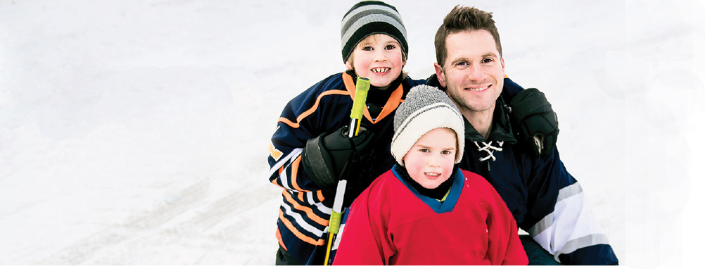 A man and two boys on the ice for Family Day