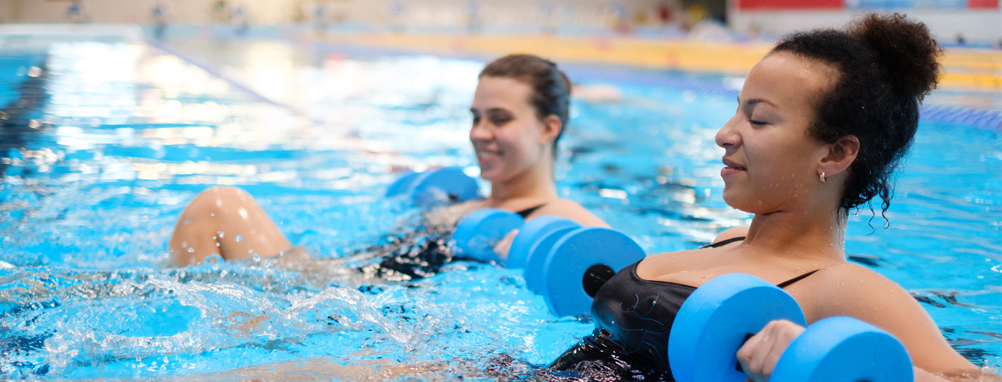 two women in the pool at aquafit class holding water barbells