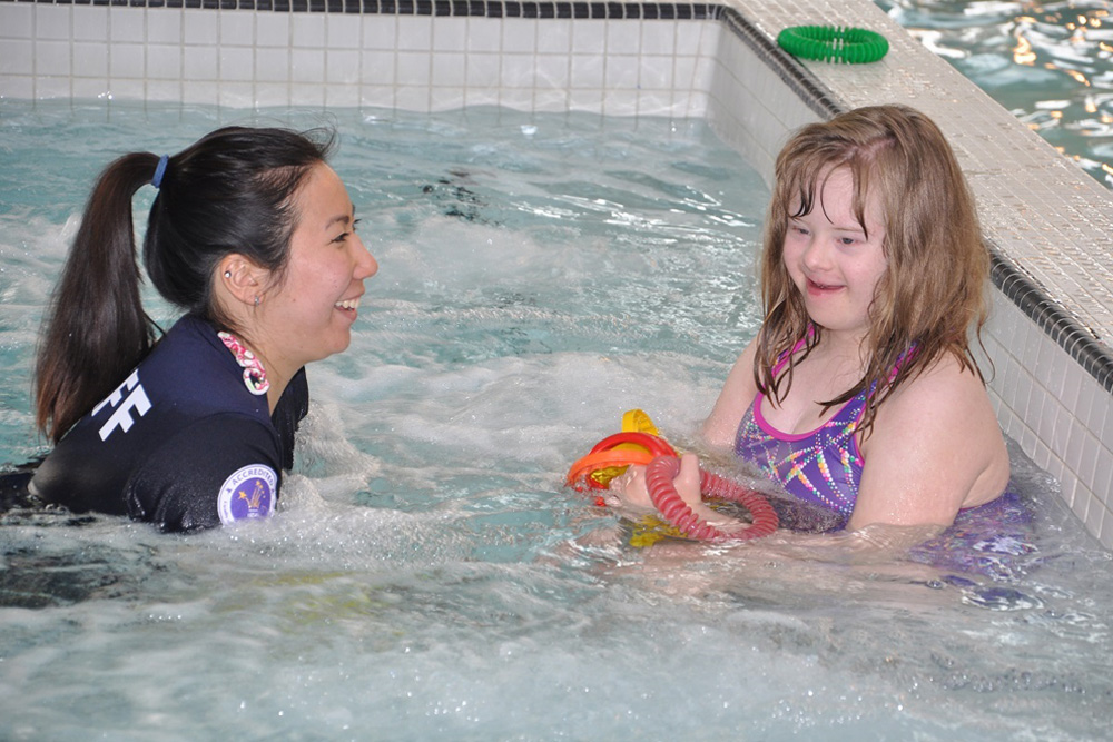 an inclusion camp counselor playing the pool with a little girl