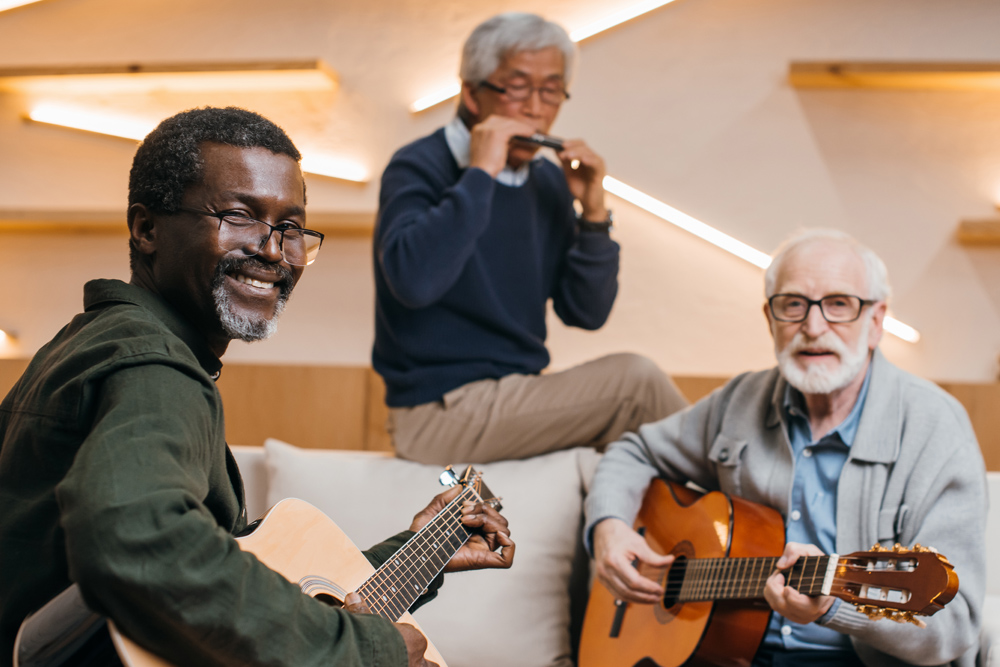 three older men playing guitars