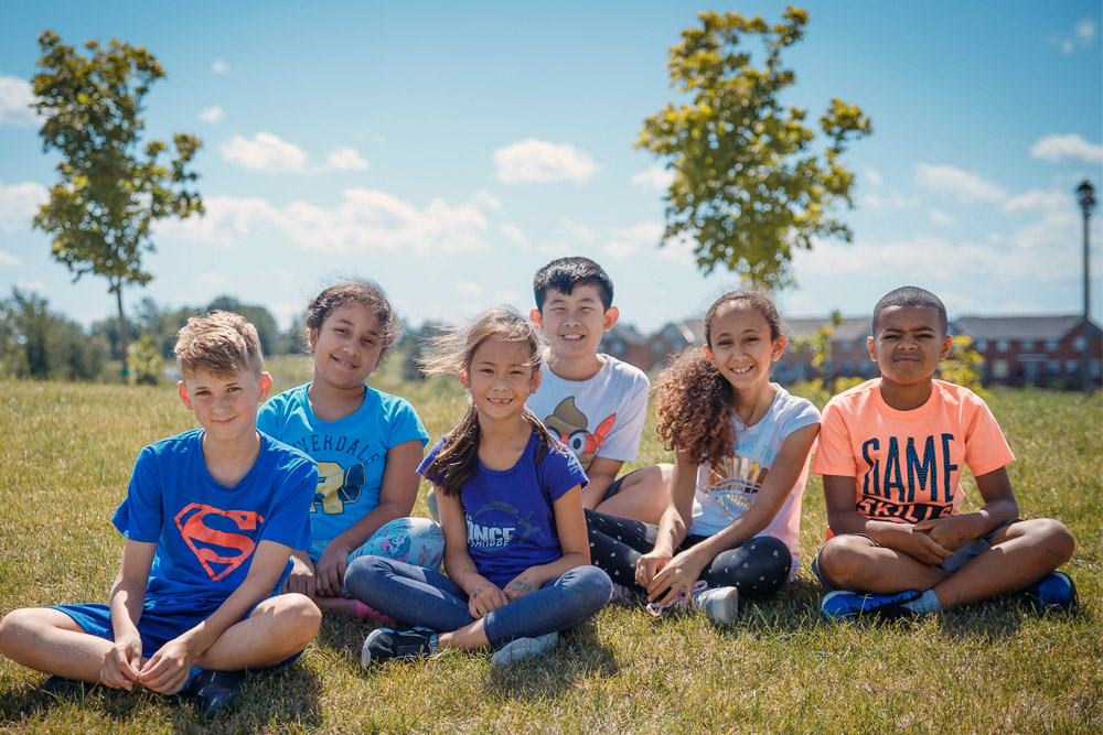 4 children sitting on a hill at summer camp