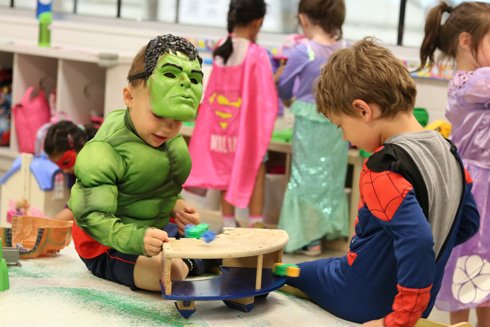 2 toddlers playing in super hero costumes on the mat in a pre-school class