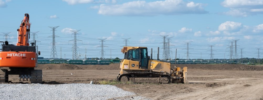 construction vehicles breaking ground on land with a go train passing in the distance.