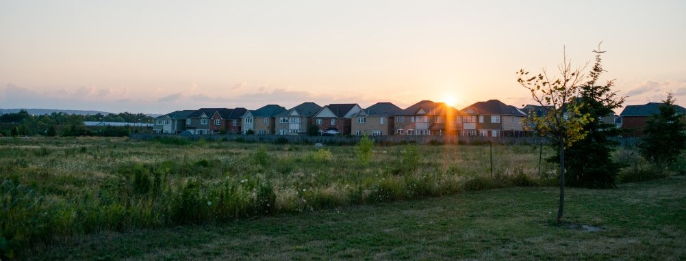 the sun setting over houses in  of a Milton neighbourhood.
