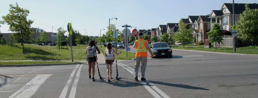 crossing guard walking 2 children across a Milton street