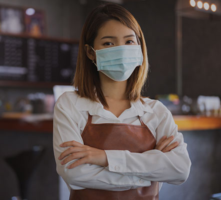 Professional woman in an apron wearing a face mask within a cafe