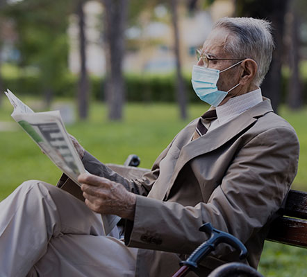 Older adult man sitting on a park bench reading the newspaper with trees and grass in the background