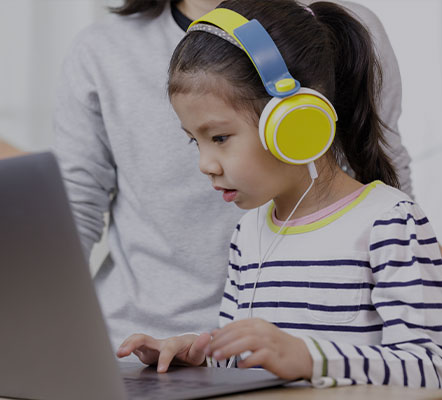 Young girl wearing headphones sitting at a table working on a laptop while a family member oversees