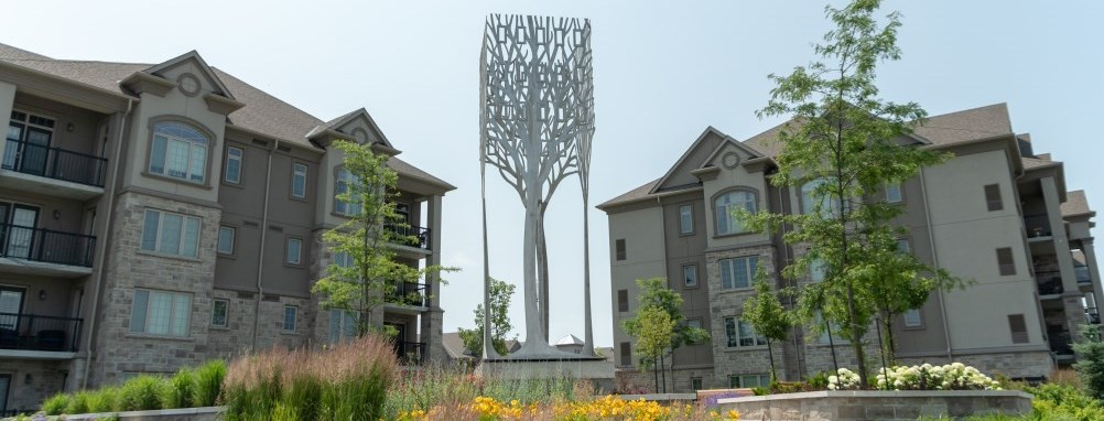 A sculpture of an abstract metal tree in a public park in Milton